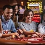 people laughing around a casino table