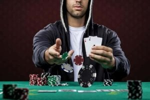 a man with poker face throwing poker chips