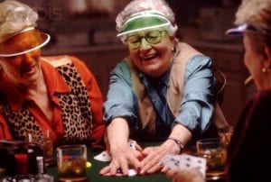 an elder woman smiling while holding poker chips