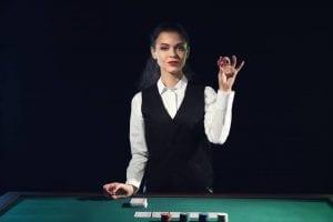 a female dealer holding a poker chip