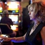 a woman sitting in front of a slot machine