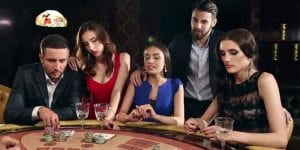 two men and three women are sitting on a poker table, thinking of their next mvoe