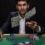 a man throwing two palying cards while sitting on a poker table