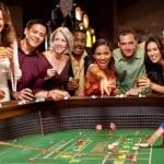 happy people sitting around a casino table