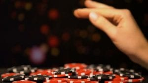 a female hand above a pile of casino chips