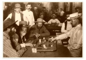 cowboys from the 1920s playing cards on a table, all of them wearing hats