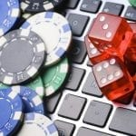 laptop keyboard with poker chips and red dices all over it