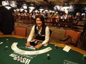 a female dealer sitting in front of a casino table