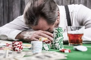 a man laying on a poker table with poker chips and a whiskey next to him